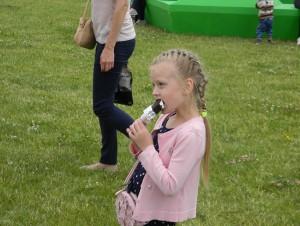 Юная жительница ЮАО ест мороженое возле летнего кафе